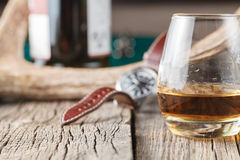Whiskey glass with watch and deer horn Royalty Free Stock Images