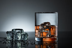 Whiskey glass with wet ice cubes royalty free stock image