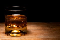 Whiskey glass and whiskey. With ice cube royalty free stock images