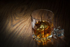 Whiskey in glass on the wood. Whiskey with ice in glass on the wood Stock Images