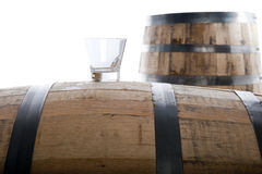 Whiskey glass on wooden barrel. Whiskey glass on a whiskey barrel with a second barrel in the distance, isolated on white, selective focus on glass Stock Photo