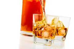 Whiskey in the glasses in front of bottle on white background Royalty Free Stock Images