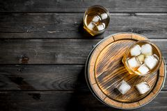 Whiskey in glasses with ice on the barrel. On black wooden background royalty free stock photos
