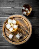 Whiskey in glasses with ice on the barrel. On black wooden background stock images