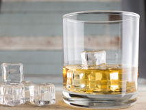 Whiskey glasses with ice cubes on old wood stock photography