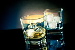 Whiskey glasses with ice and light tint blue disco on black background Royalty Free Stock Photos