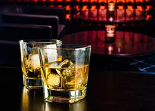 Whiskey glasses with ice in a lounge bar. On wood table Royalty Free Stock Images