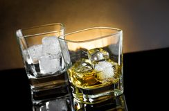 Whiskey glasses with ice and warm light on black background Stock Images