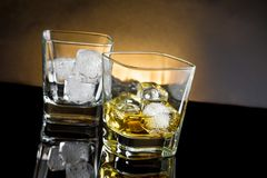 Whiskey glasses with ice and warm light on black background royalty free stock photo