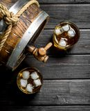 Whiskey in glasses with ice and a wooden barrel. On wooden background stock photo