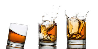 Whiskey glasses with splash, isolated on white Stock Photos