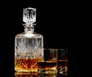 Whiskey on a glossy table. Studio shot of whiskey in a carafe and glasses isolated on black Stock Image