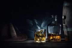 Whiskey and hat and barrel on dark background. Whiskey and hat and barrel on dark marble background royalty free stock images