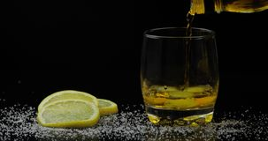 Whiskey with ice. Pouring whisky rum from the bottle on black background royalty free stock images