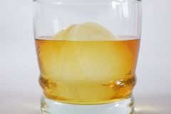 Whiskey on Ice. Close up of a glass of whiskey with a sphere icecube Stock Photography
