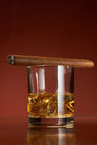 Whiskey with ice cubes and cigar, on brown royalty free stock photo