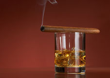 Whiskey with ice cubes and cigar, on brown Stock Photo