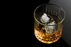 Whiskey with ice cubes in glass on black background Royalty Free Stock Photography