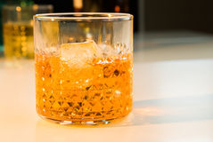 Whiskey with ice cubes in glass with bottle in background Stock Photos