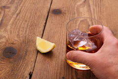 Whiskey with ice cubes in glass with grab hand Royalty Free Stock Photos