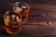 Whiskey with ice cubes on wooden table, copy space.  Alcohol dri. Nks, bar concept Stock Images