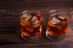 Whiskey with ice cubes on wooden table, copy space.  Alcohol dri. Nks, bar concept Royalty Free Stock Photos