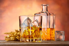Whiskey with ice and ears of wheat Stock Photo