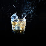 Whiskey with ice falling into glass solated on black Stock Photography