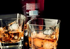 Whiskey with ice in glass on black background near bottle Stock Images