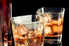 Whiskey with ice in glass on black background near bottle Royalty Free Stock Photos
