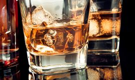 Whiskey with ice in glass on black background near bottle Royalty Free Stock Image