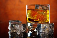 Whiskey and ice. Glass of whiskey and ice cubes on dark reflective table , red background Stock Photos