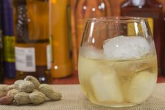 Whiskey with ice. Whiskey glass with ice in front of bottles, peanuts on the table Stock Photography