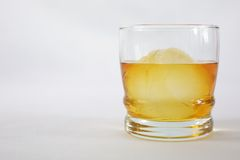 Whiskey on Ice. A glass of whiskey with a sphere ice cube Stock Images