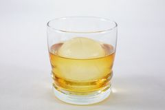 Whiskey on Ice. A glass of whiskey with a sphere shaped ice cube against a white background stock photo