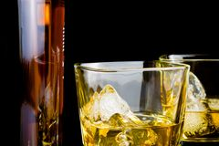 Whiskey with ice in glasses in front of bottle on black background Stock Images