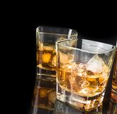 Whiskey with ice in glasses near bottle on black background Royalty Free Stock Photography