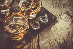 Whiskey with ice in glasses. Rustic wood background, copy space royalty free stock images