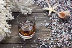 Whiskey with ice. Whiskey on the rocks near the sea shells on the table Royalty Free Stock Photography