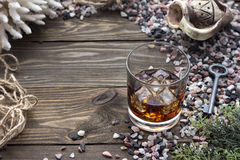 Whiskey with ice. Whiskey on the rocks near the sea shells on the table Stock Images