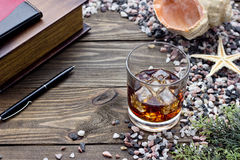Whiskey with ice. Whiskey on the rocks among the sea rocks Royalty Free Stock Photos