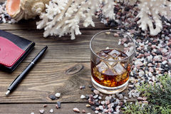 Whiskey with ice. Whiskey on the rocks among the sea rocks Royalty Free Stock Photo