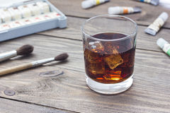 Whiskey with ice. On a table near the paint Royalty Free Stock Image