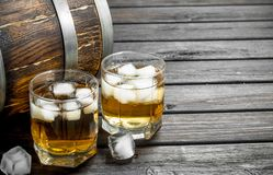 Whiskey with ice and a wooden barrel. On black wooden background stock image