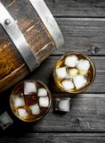 Whiskey with ice and a wooden barrel. On black wooden background stock photography