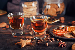 Whiskey or liqueur, cookies, spices and decorations on wooden ba stock images