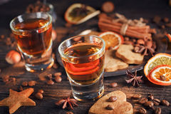 Whiskey or liqueur, cookies, spices and decorations on wooden ba royalty free stock photo