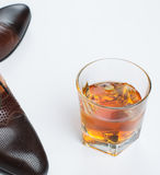 Whiskey and male shoes over white Royalty Free Stock Images