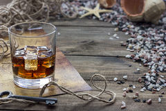 Whiskey and map. Hiskey and cards are on the table among the shells Royalty Free Stock Image