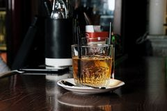 Whiskey and natural ice on old wooden table stock photography